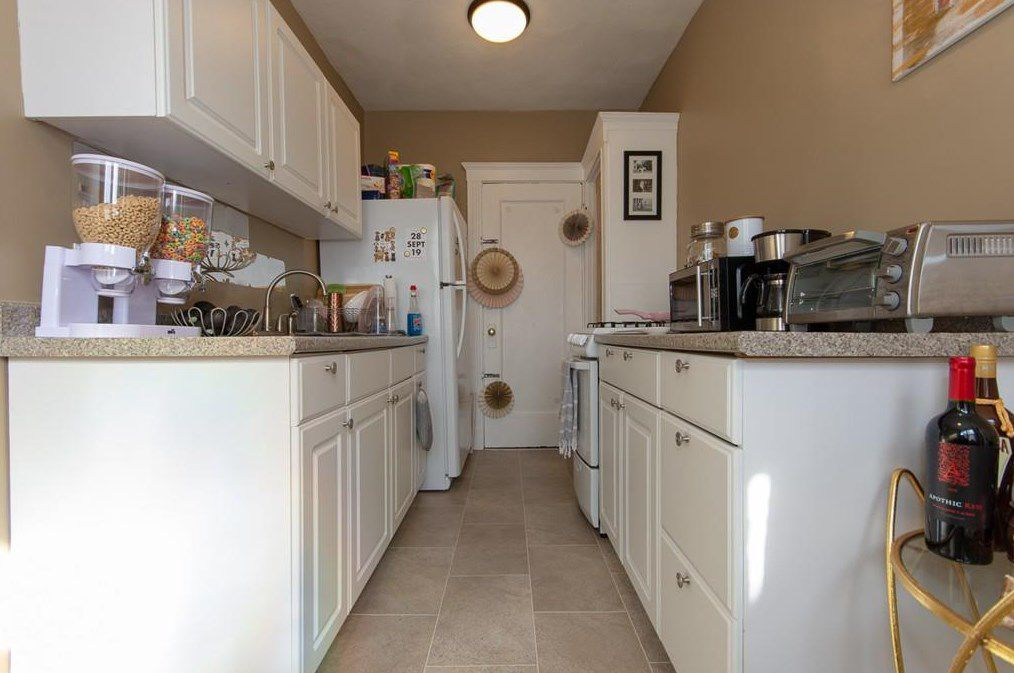 A narrow, long kitchen with counters on either side.