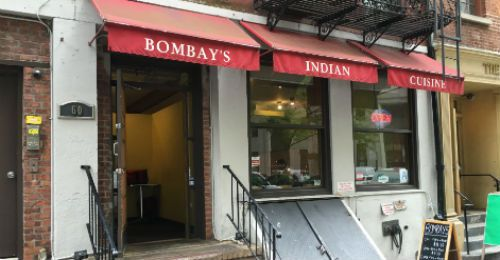 The exterior of a restaurant with a red awning with the sign Bombay emblazoned on it