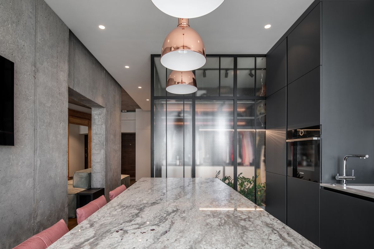 Kitchen with marble counter and pink bar stools.