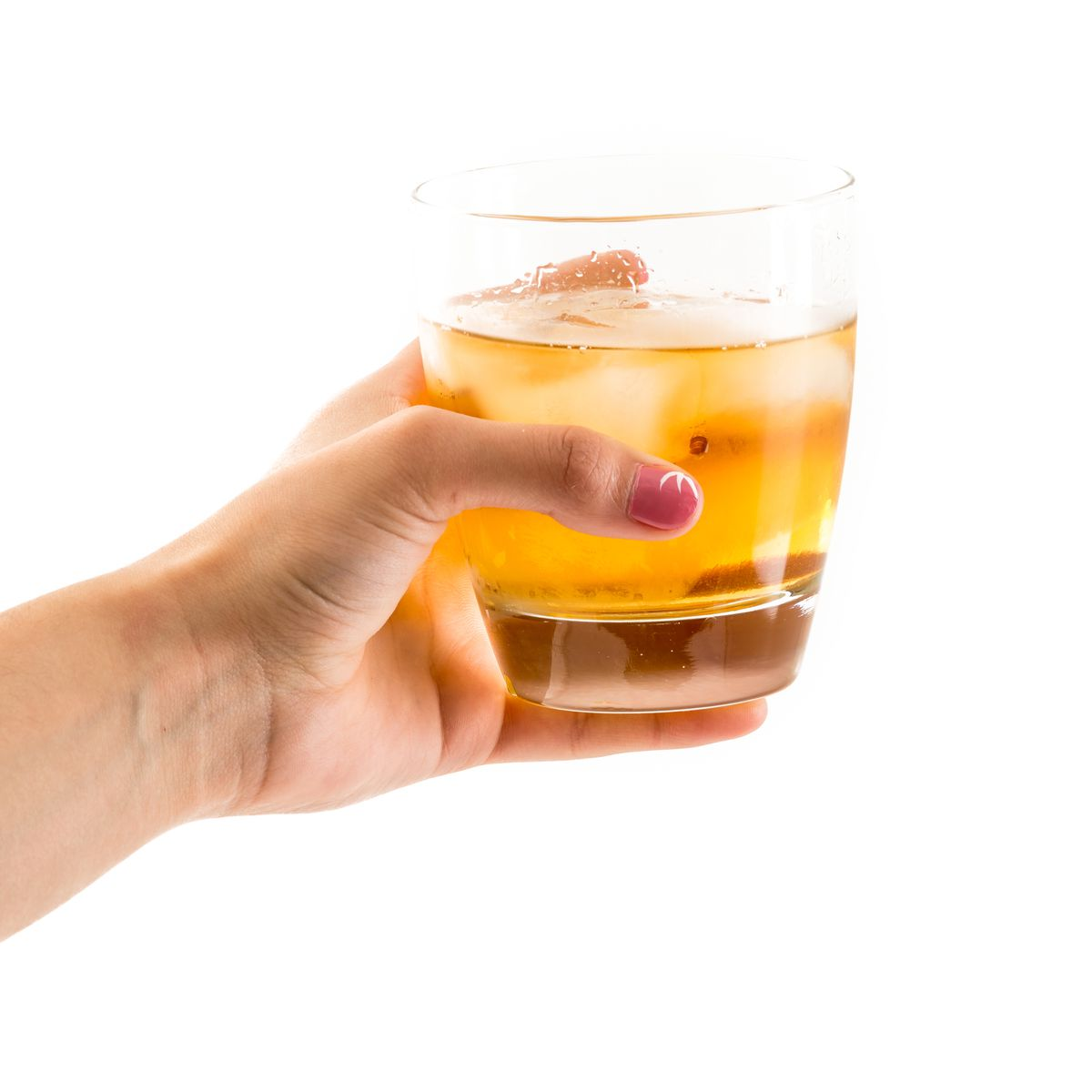 Hand holding an old fashioned glass with whisky on the rocks...