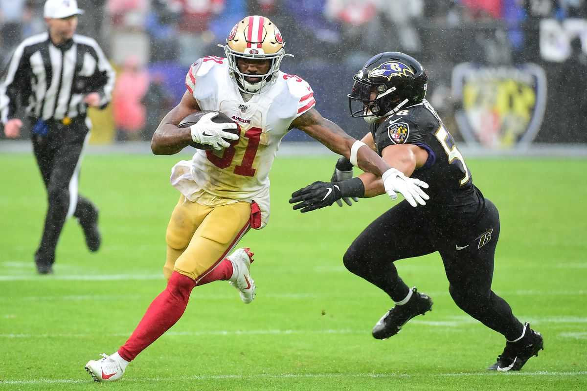 San Francisco 49ers running back Raheem Mostert runs with the ball while being pursued by Baltimore Ravens linebacker L.J. Fort in the second quarter at M&T Bank Stadium.