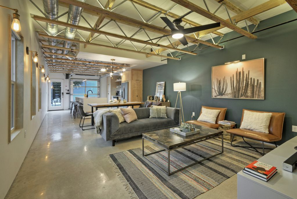 Large, open living-dining-kitchen area with contemporary, simple chairs, couch, and coffee table in foreground and dining and kitchen area in back,. It has polished concrete floors and exposed ducts and ceiling beams. Windows line two walls.