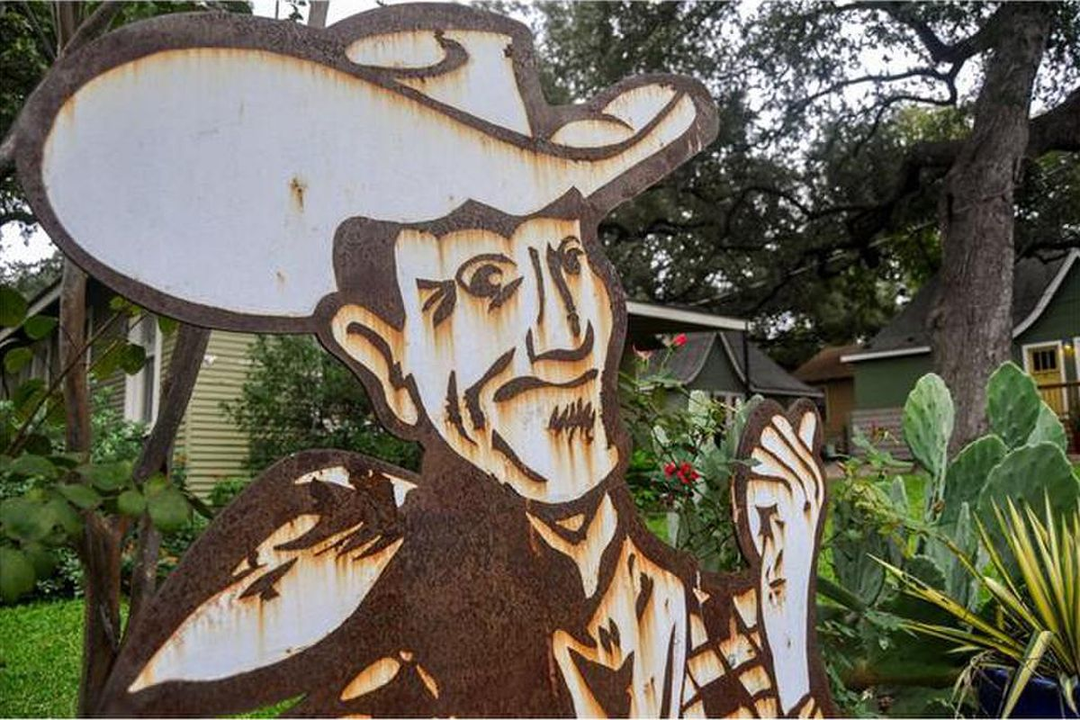 Weathered metal sign of a cowboy with thumb pointing at foliage