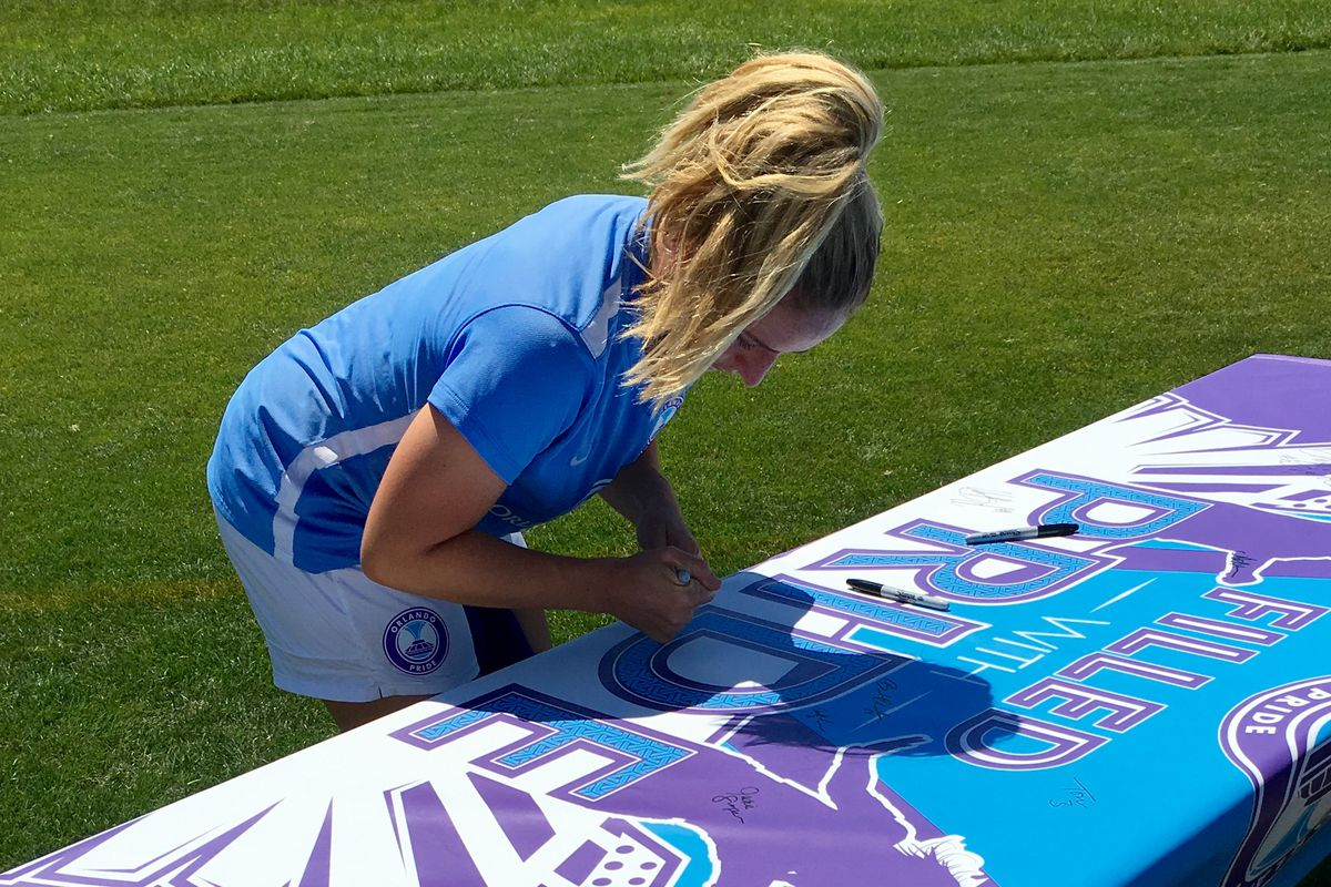 Cami Levin signs #FilledWithPride banner after practice