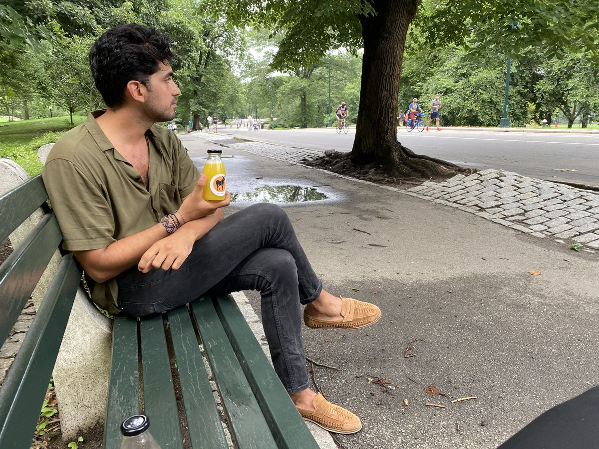 A man sits on a green bench holding a drink in his hand