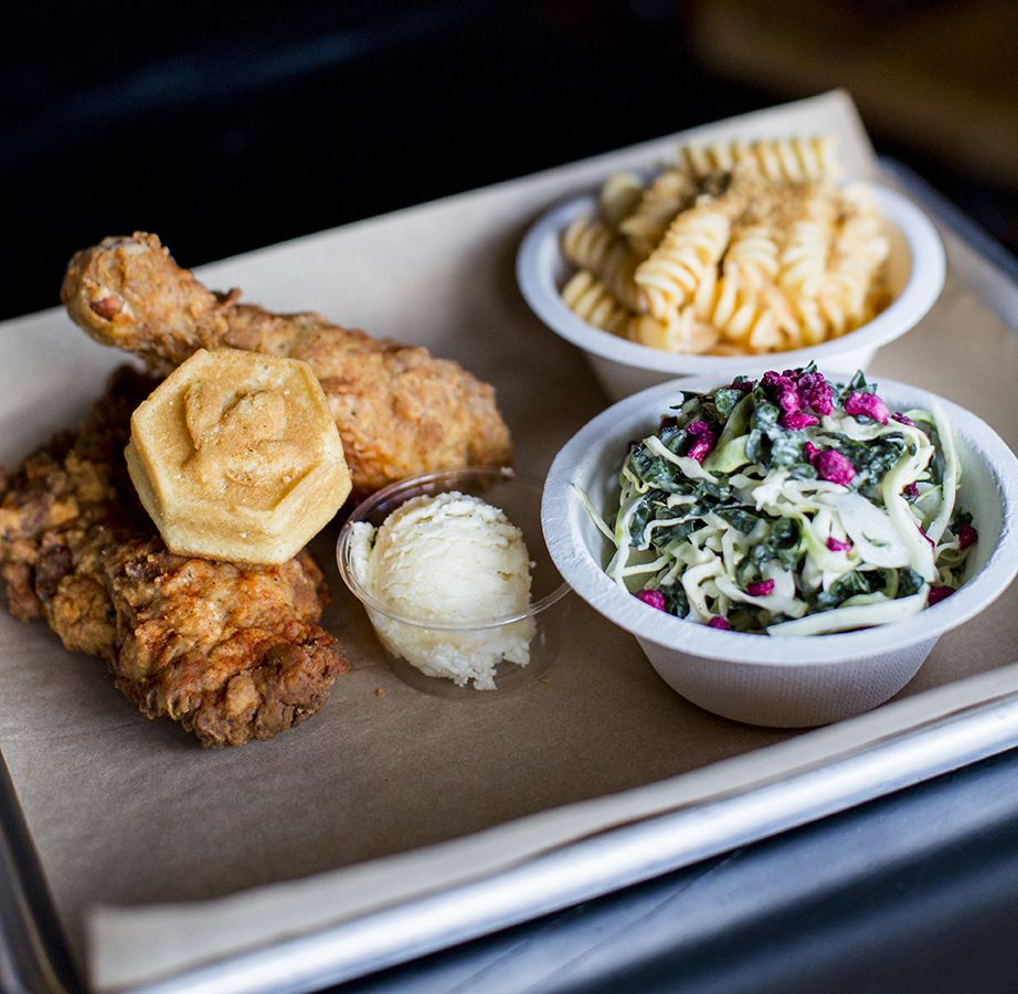 A small tray contains two pieces of fried chicken, a bowl of mac and cheese, and a bowl of salad.