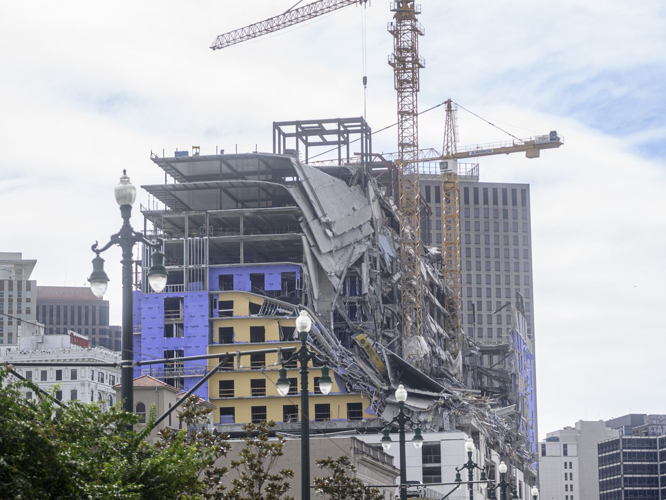 A collapsed hotel with two large cranes hovering above it faces Canal Street