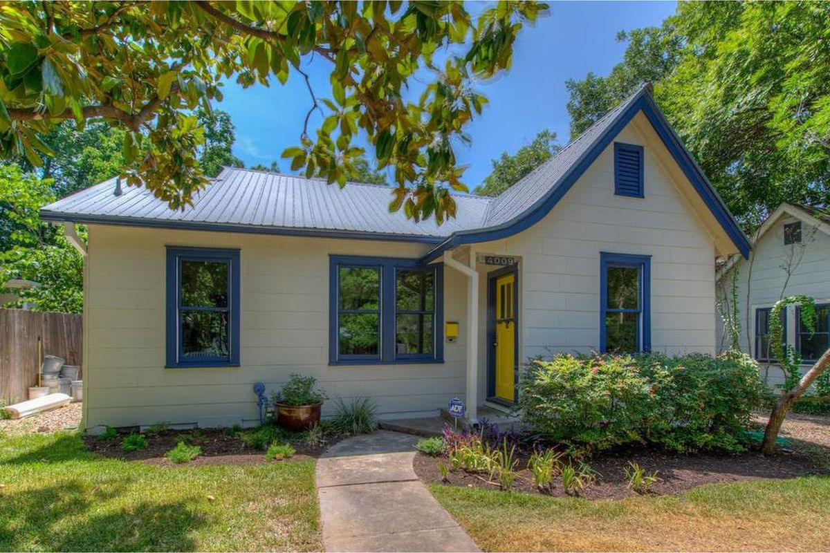 small white 1939 house with blue trim and metal roof