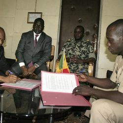 Coup leader Capt. Amadou Haya Sanogo, right, and Burkina Faso Foreign Minister Djibrill Bassole, left, sign documents as part of an accord agreeing that Sanogo will return the country to constitutional rule, in Sanogo's office at junta headquarters in Kati, outside Bamako, Mali Friday, April 6, 2012. Under intense pressure from the nations bordering Mali, the junior officer who seized control of the country in a coup last month signed an accord agreeing to return the country to constitutional rule. The announcement was made late Friday, only hours after separatist rebels in the country's distant north declared their independence.