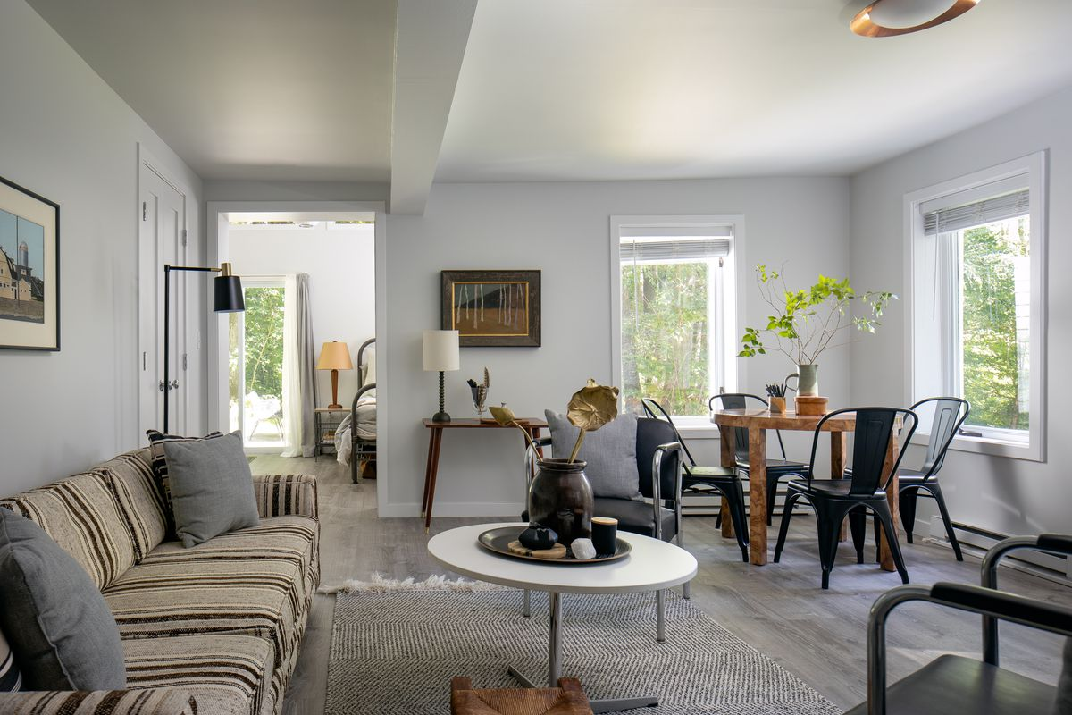 A living room has a striped couch, white coffee table, and a dining room table in the corner.