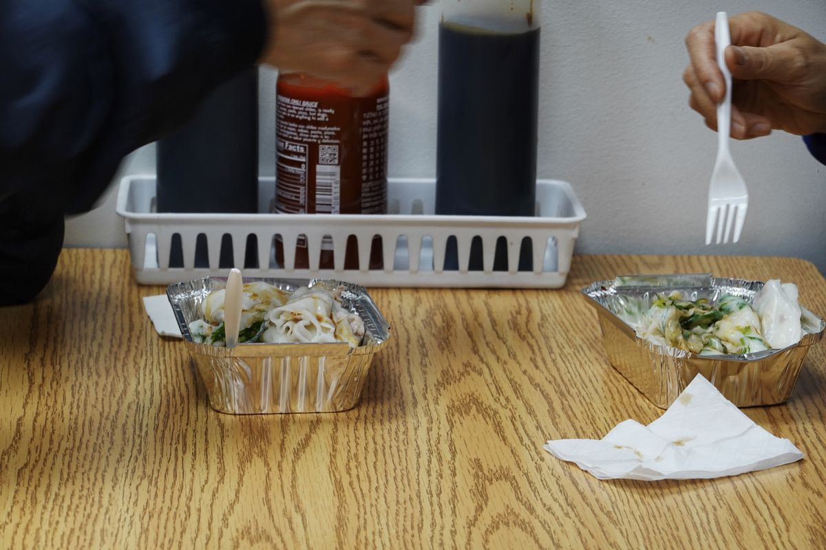 Small metal boxes hold fresh rice rolls as customers dive in with plastic forks