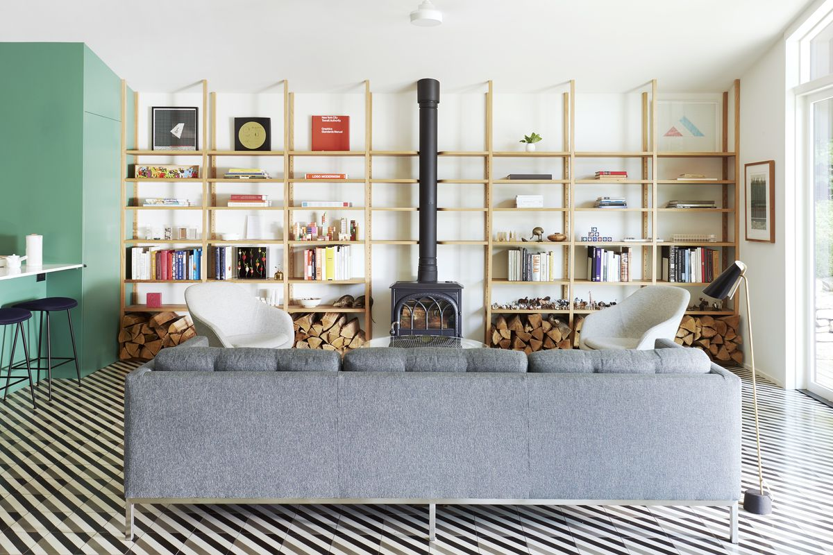 A grey couch sits in front of a living room with a wood burning stove as the focal point. To the stoves left and right are floor-to-ceiling wooden shelves that are minimally stacked with books, art, and colorful trinkets. The floor is a tiled diagonal white, grey and black striped pattern.