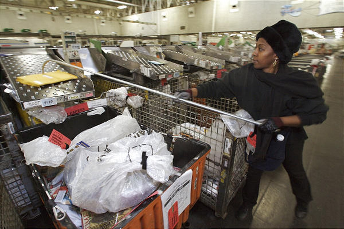 Postal employee Lucretia Thomas sorts mail in Los Angeles last year. Recession has hit the Postal Service hard.