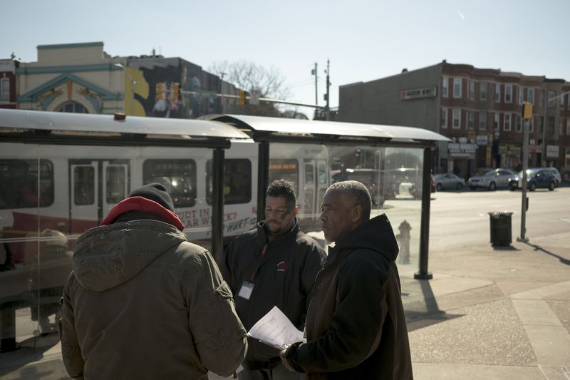 Aaron Robinson (right) and Wayne Stokes (center), with the Recovery Network provide information on free services for opioid addiction recovery in West Baltimore.