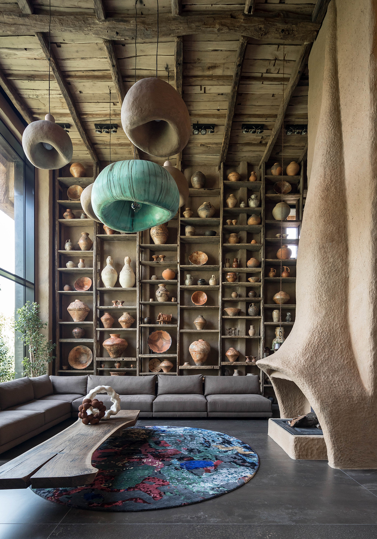 A double-height living room with an rounded fireplace leading up to the ceiling and a full wall of ceramics.