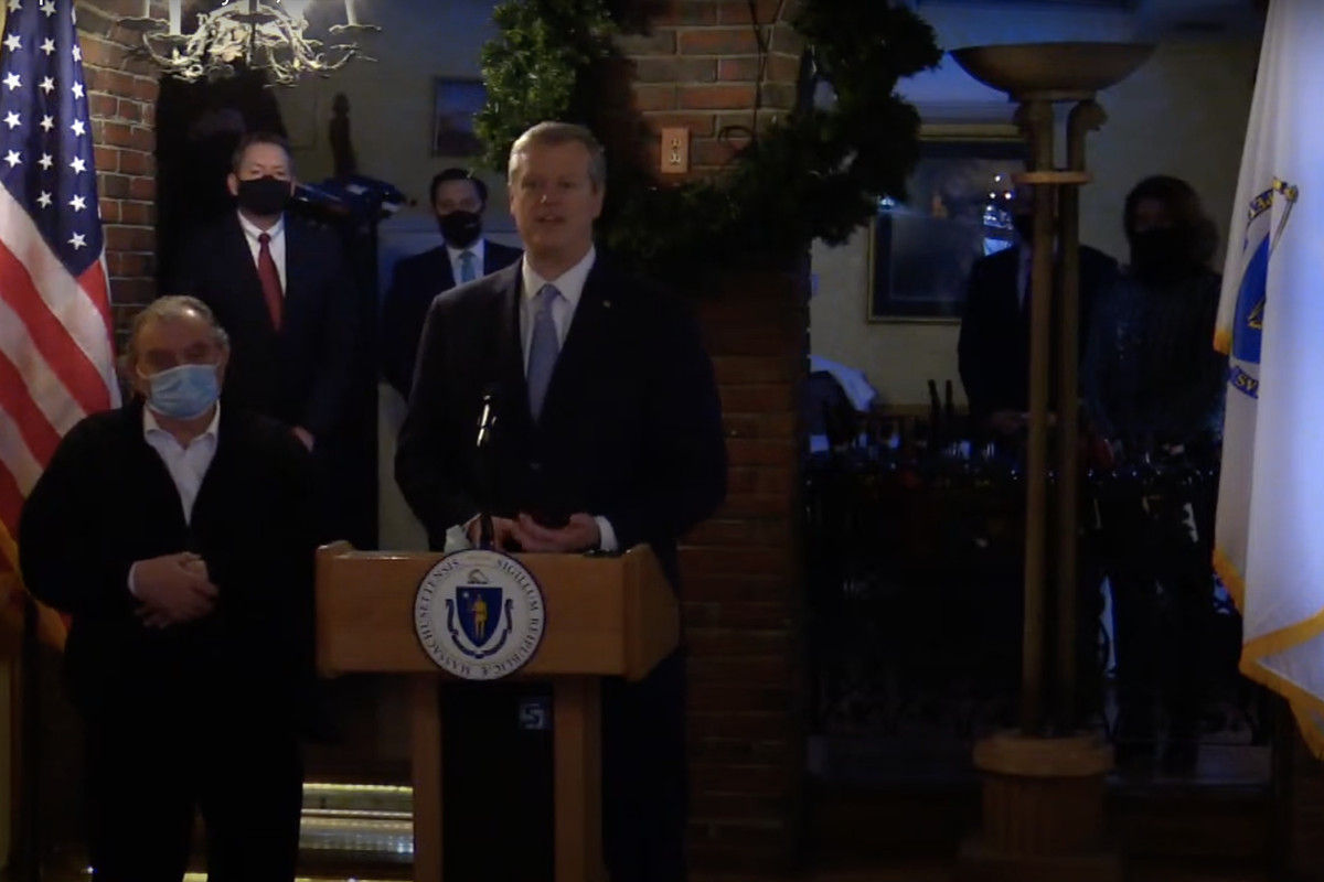 Interior of a restaurant in Boston's north end with yellow walls and exposed brick. MA Gov. Charlie Baker stands next to the restaurant's owner.
