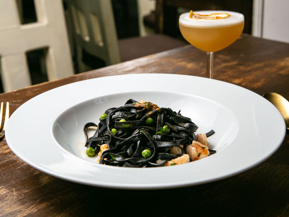 dark noodles in a large white bowl near a cocktail