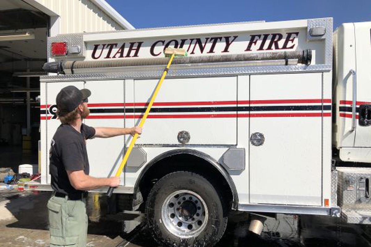 A member of the Utah County Fire Department helps wash trucks and equipment after returning from three weeks fighting wildfires in California on Saturday, Sept. 5, 2020.