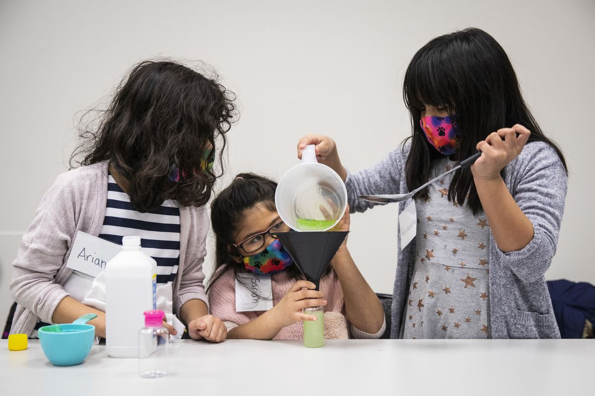 (From left) Sisters Arianna, Sariah and Alessandra Stagen demonstrate how they made a batch of homemade hand sanitizer to donate to the Chicago Police Department during a press conference with Supt. David Brown at CPD headquarters, Wednesday afternoon, April 29, 2020.