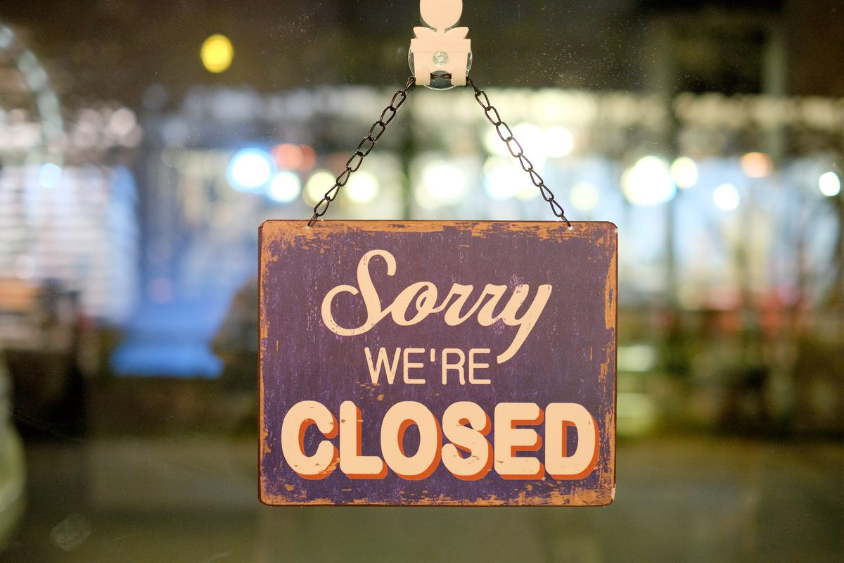 """A """"sorry, we're closed"""" sign hangs on the outside of a restaurant"""