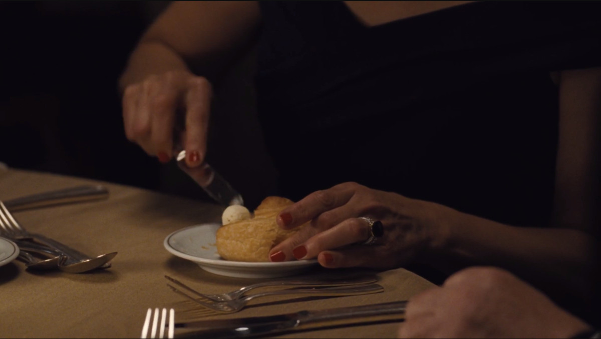 Succession screenshot: Marcia's hands spreading cold butter on a dinner roll.