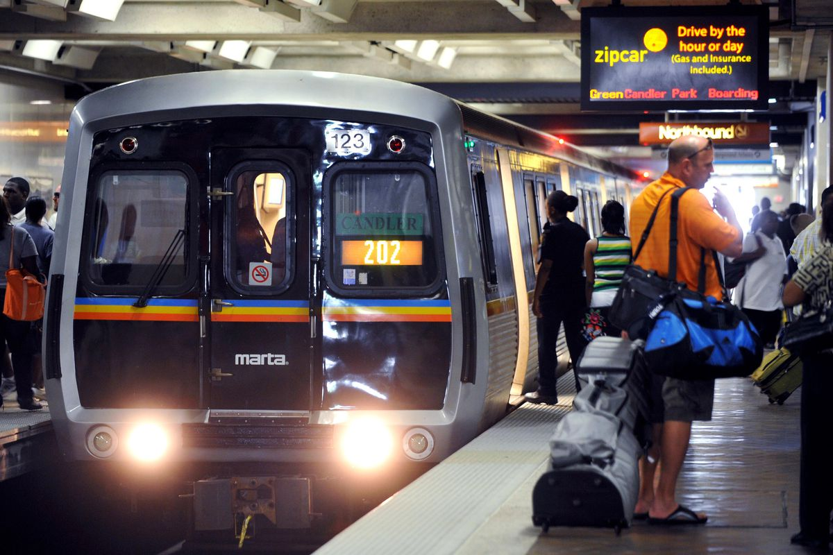 A MARTA train arriving at a crowded platform at Five Points Station.