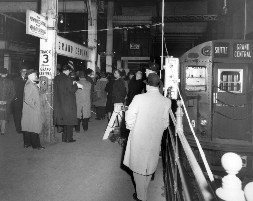 Black and white photo of the Grand Central station, several people waiting to board the shuttle train.