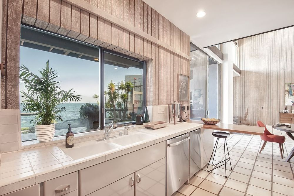 A midcentury modern kitchen with wood paneled walls, white tiled countertops, chairs, and a table. There is a window over the sink looking out onto a beach.