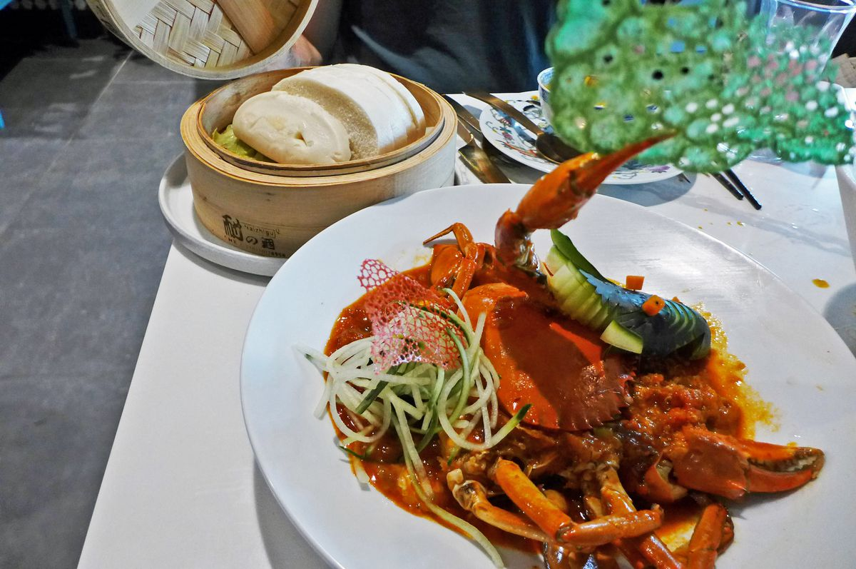 A bowl of crab curry has an entire red crab in it and comes with a steamer of mantou, seen in the background...