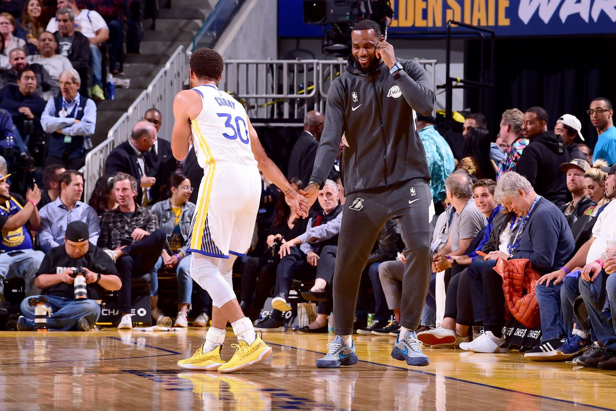 Stephen Curry of the Golden State Warriors talks with LeBron James of the Los Angeles Lakers during a pre-season game on October 18, 2019 at Chase Center in San Francisco, California.