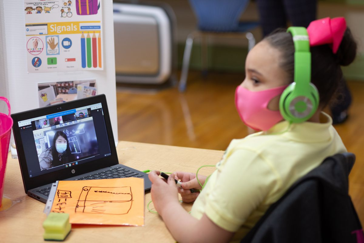 A young girl wearing a yellow shirt, pink mask, and green headphones sits at a partitioned desk in a classroom and watches her teacher on a small laptop.