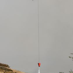 A helicopter works to extinguish a brush fire at the base of Mount Timpanogos in Orem on Saturday, Oct. 17, 2020.