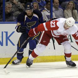 St. Louis Blues' Matt D'Agostini, left, and Detroit Red Wings' Brad Stuart chase after a loose puck during the second period of an NHL hockey game on Wednesday, April 4, 2012, in St. Louis.