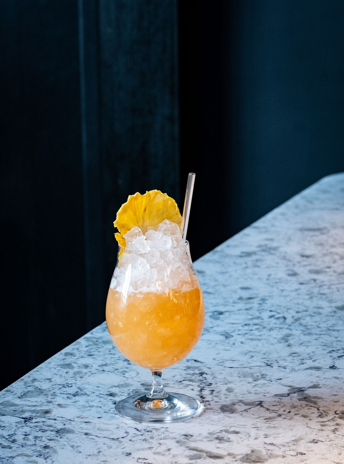 An orange cocktail is served on a marble bar top with a deep blue curtain in the background