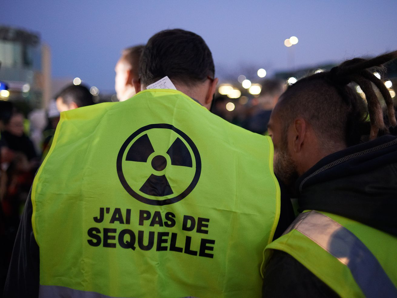"""A protester in a yellow vest that reads """"J'ai pas de sequelle"""" in French, """"I have no after-effects"""" in English."""