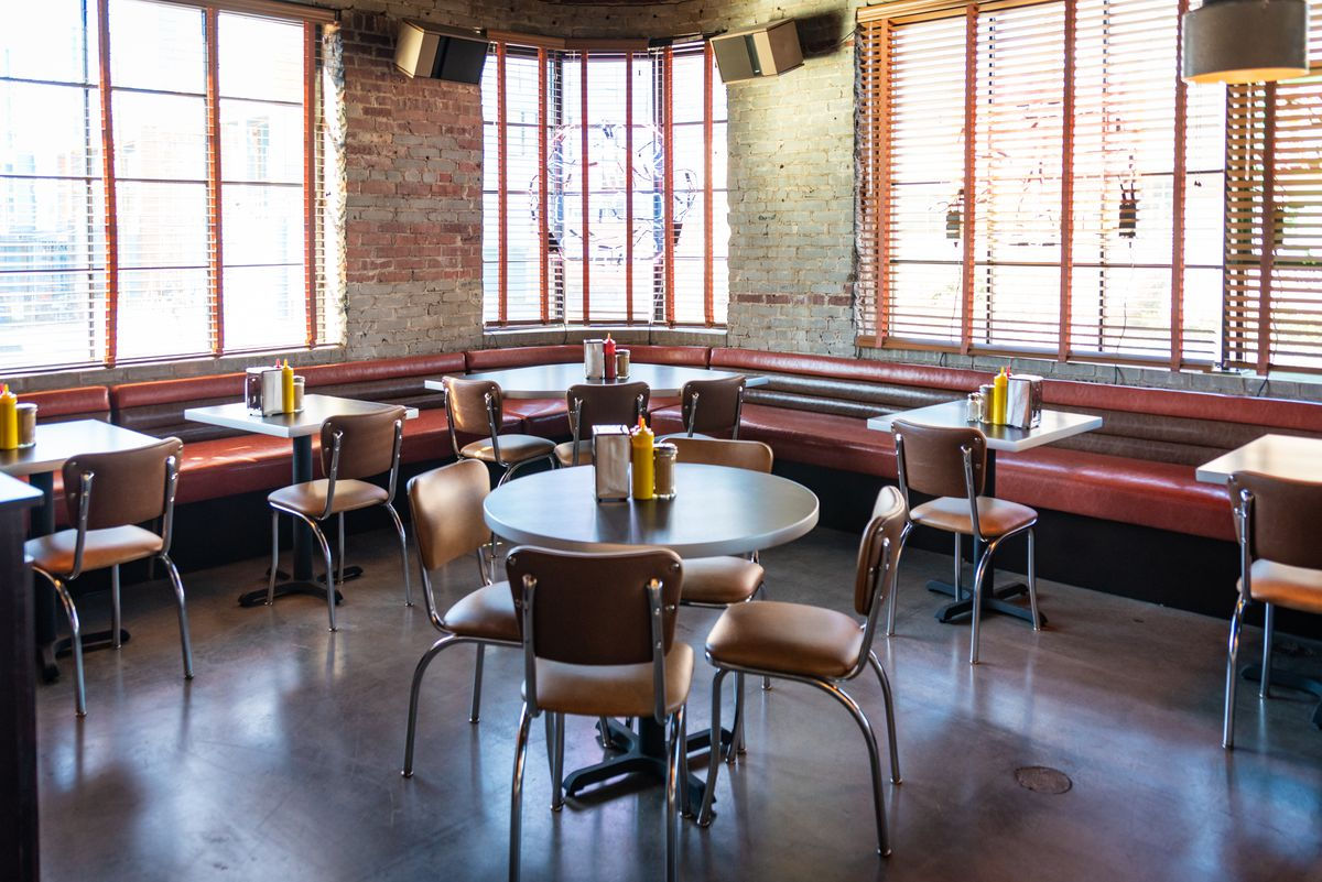 A dining area with vintage diner tables and chairs and a banquette along the wall at Wonderkid at Atlanta Dairies