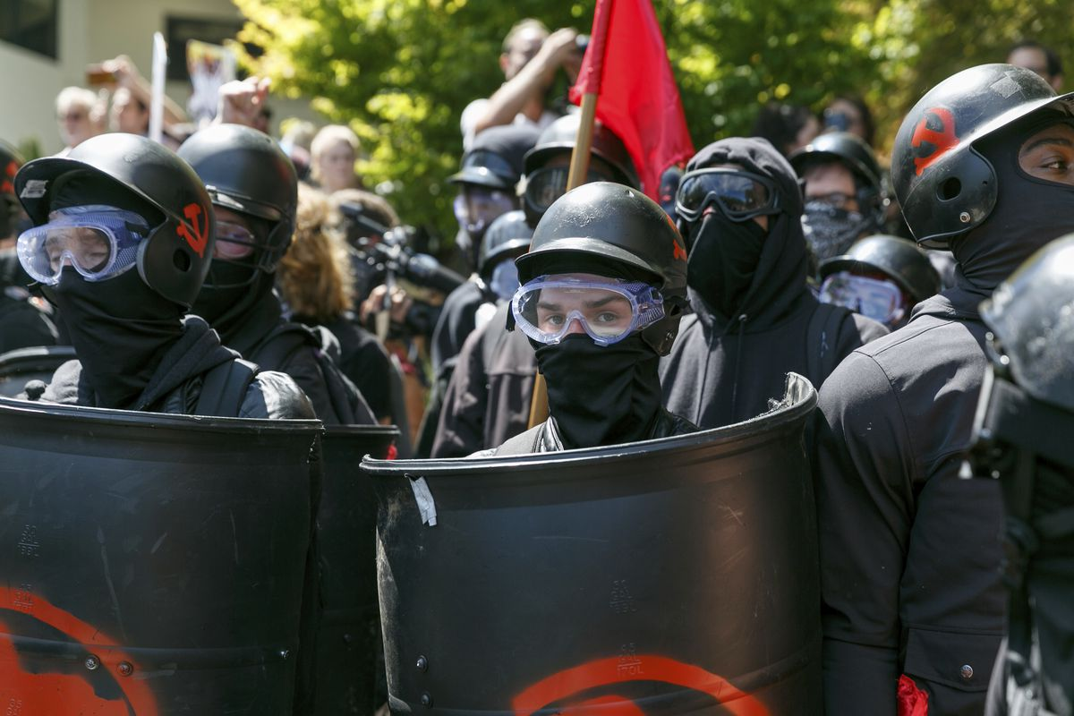 A masked antifa protester stands with fellow anti-fascists during a rally in Portland, Oregon, on Aug. 4, 2018.