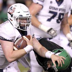 Utah State quarterback Logan Bonner (1) stiff arms North Dakota defensive back Hayden Galvin (17) during the second half of an NCAA college football game Friday, Sept. 10, 2021, in Logan, Utah.
