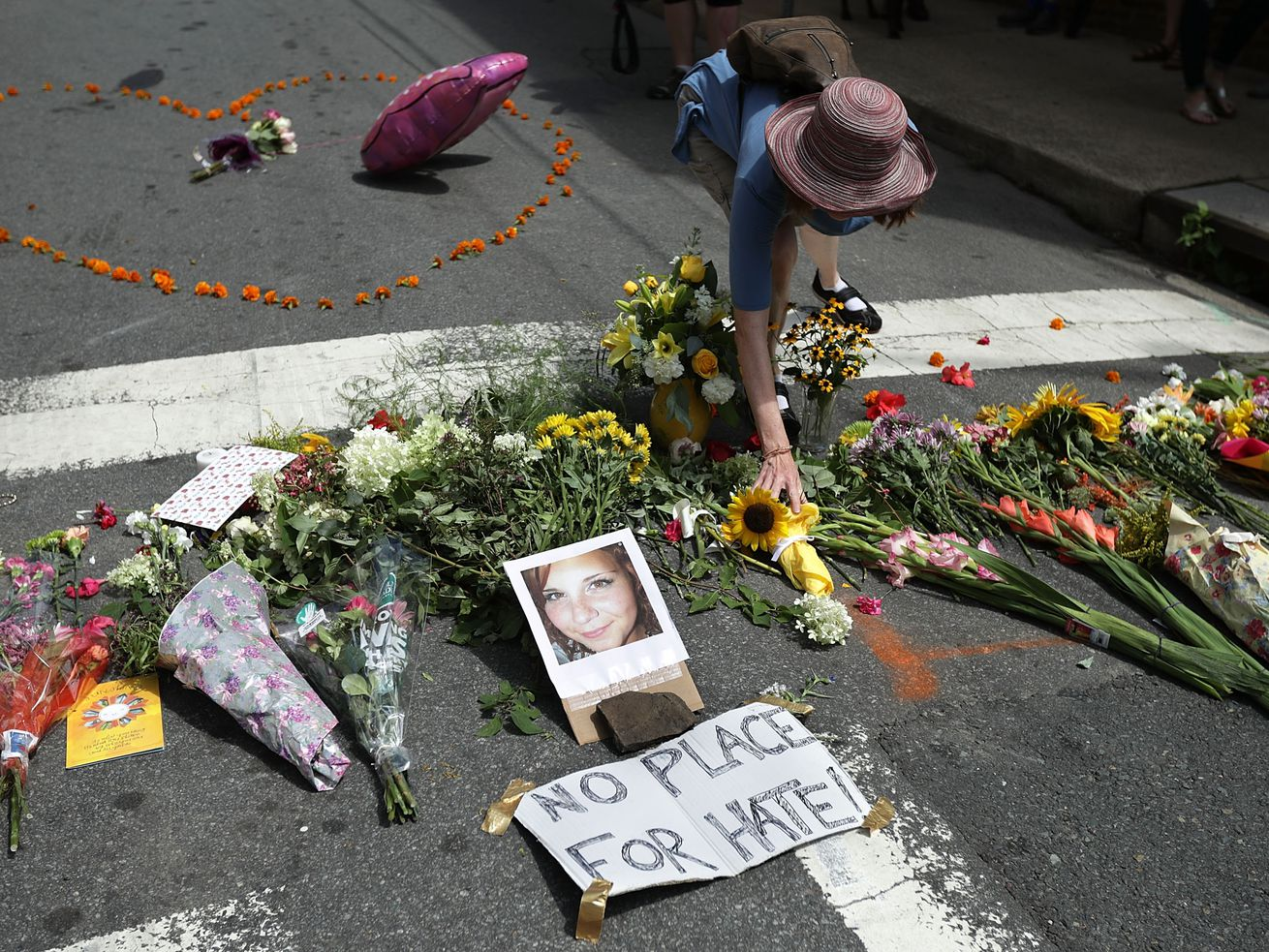A woman places flowers at an informal memorial to 32-year-old Heather Heyer, who was killed when a car plowed into a crowd of people protesting against the white supremacist Unite the Right rally, August 13, 2017, in Charlottesville, Virginia.