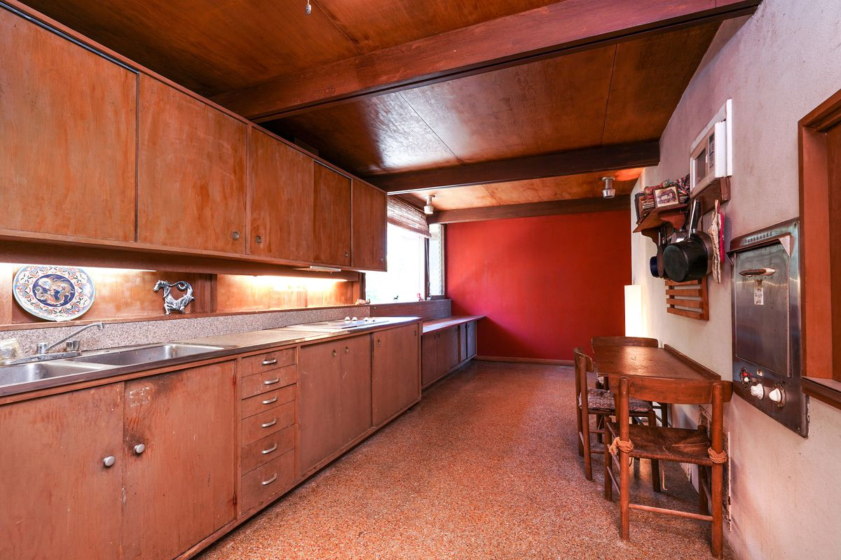 A long kitchen has worn wood cabinets and a small table for eating.