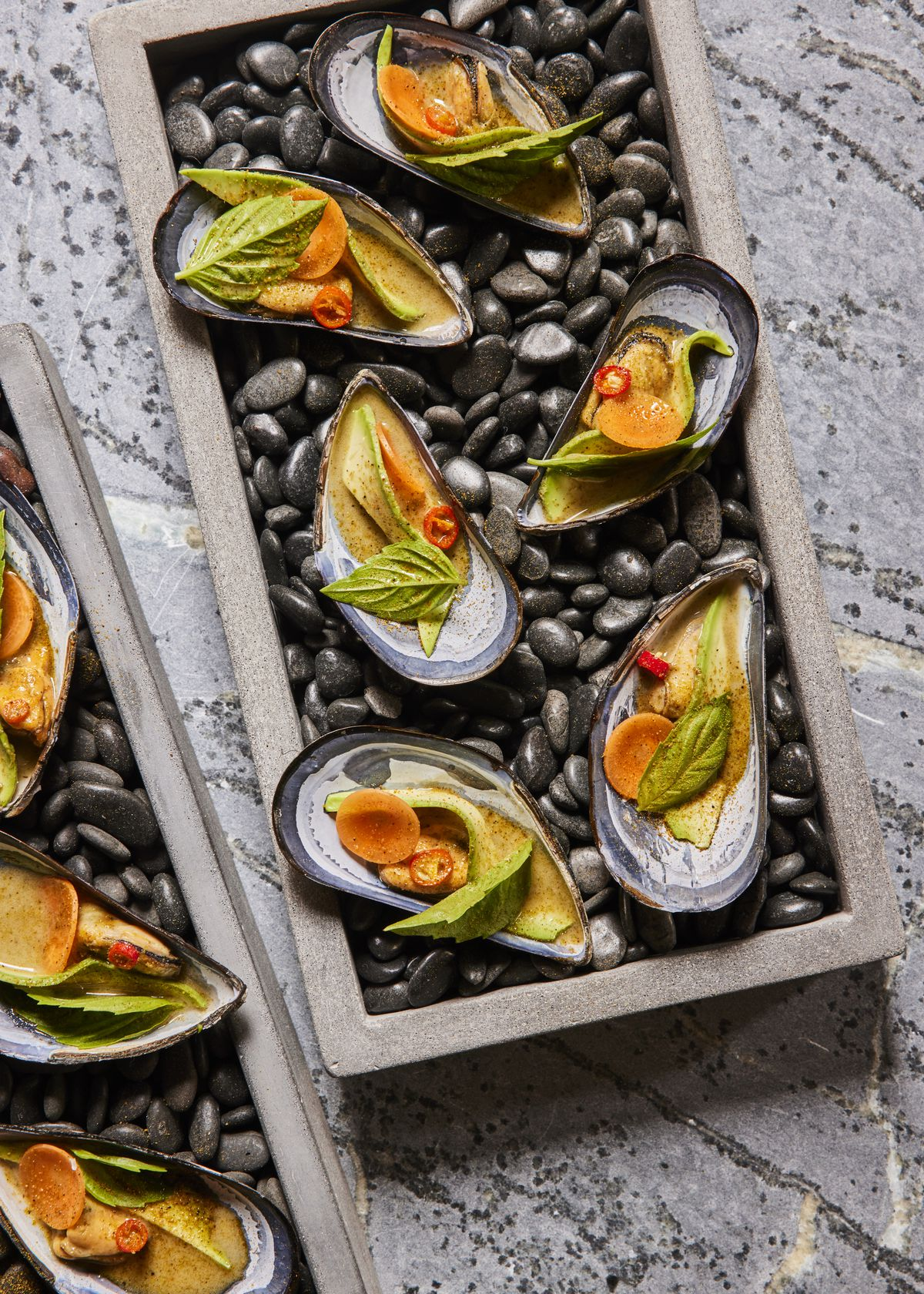 An overhead photograph of a tray of a half-dozen mussels filled with green leaves, and an orange-colored broth