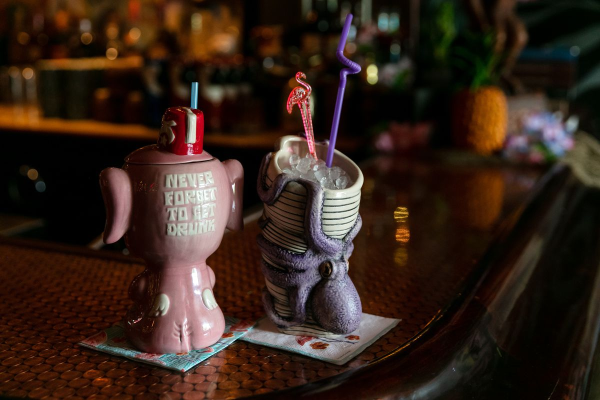 """A pink elephant mug that reads """"Never Forget to Get Drunk"""" and a purple octopus mug sit on a penny-topped bar at Lost River."""