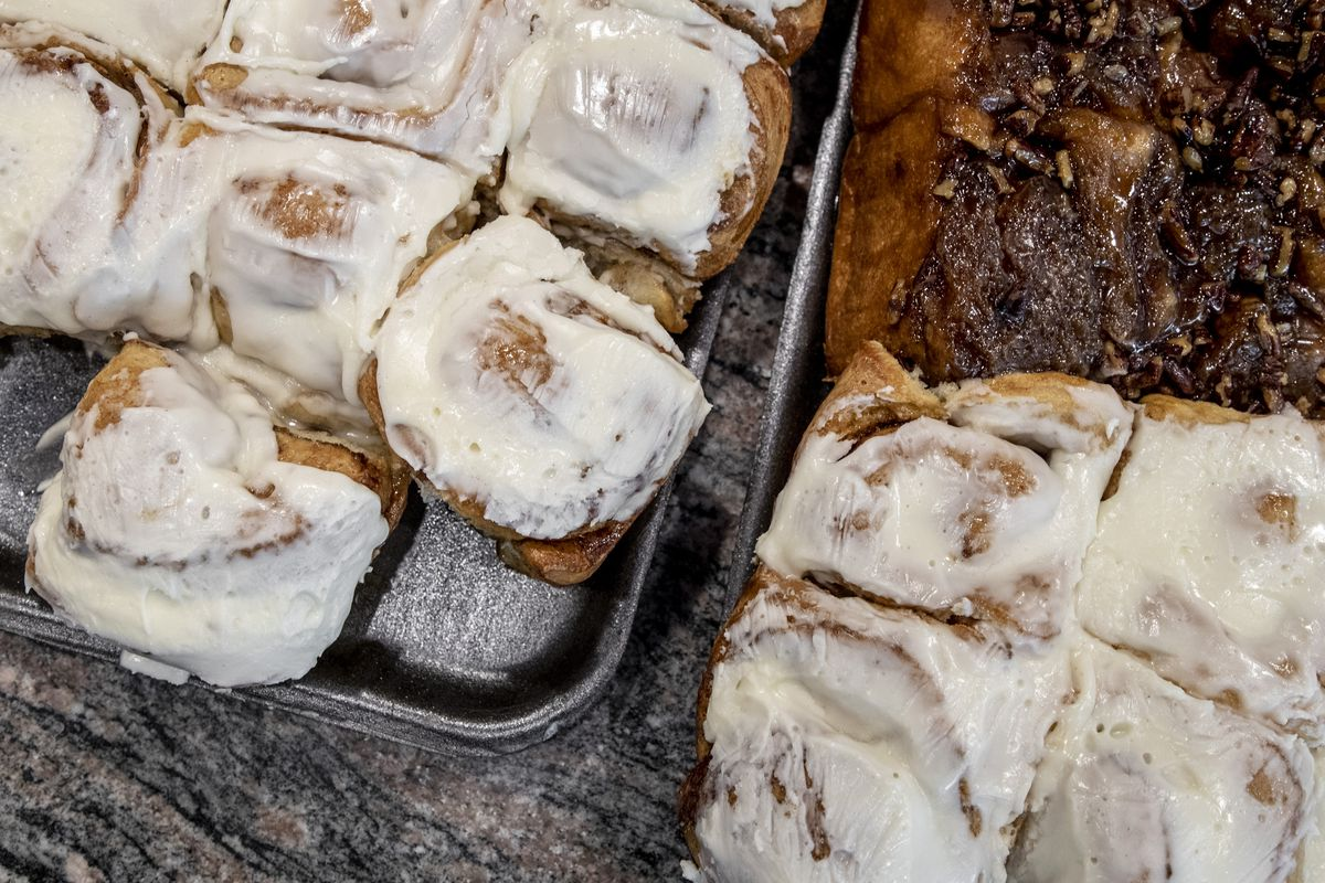Cinnamon rolls and pecan buns on metal trays.