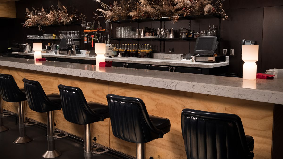 The elegant bar at Marvel, with black barstools, the back is filled with dried florals where the bottles of liquor would usually be.