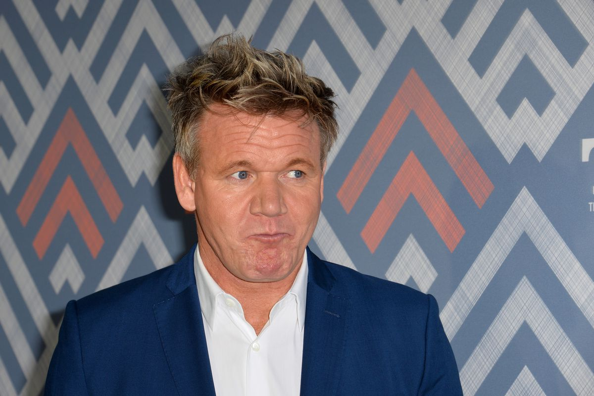 Gordon Ramsay wears a suit against a chevron-printed background, while pulling a strange face