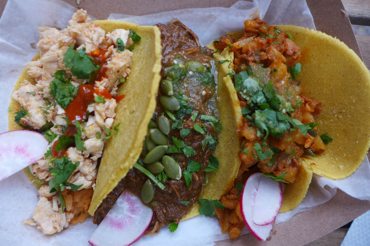 Three tacos, the middle one chicken mole with pumpkin seeds sprinkled on top.
