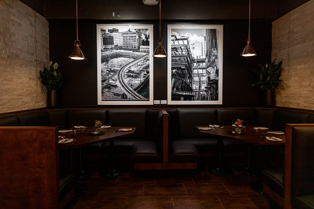 Two black and white photos of downtown Detroit under construction hang above two booths with black upholstery lit by silver pendant lights.