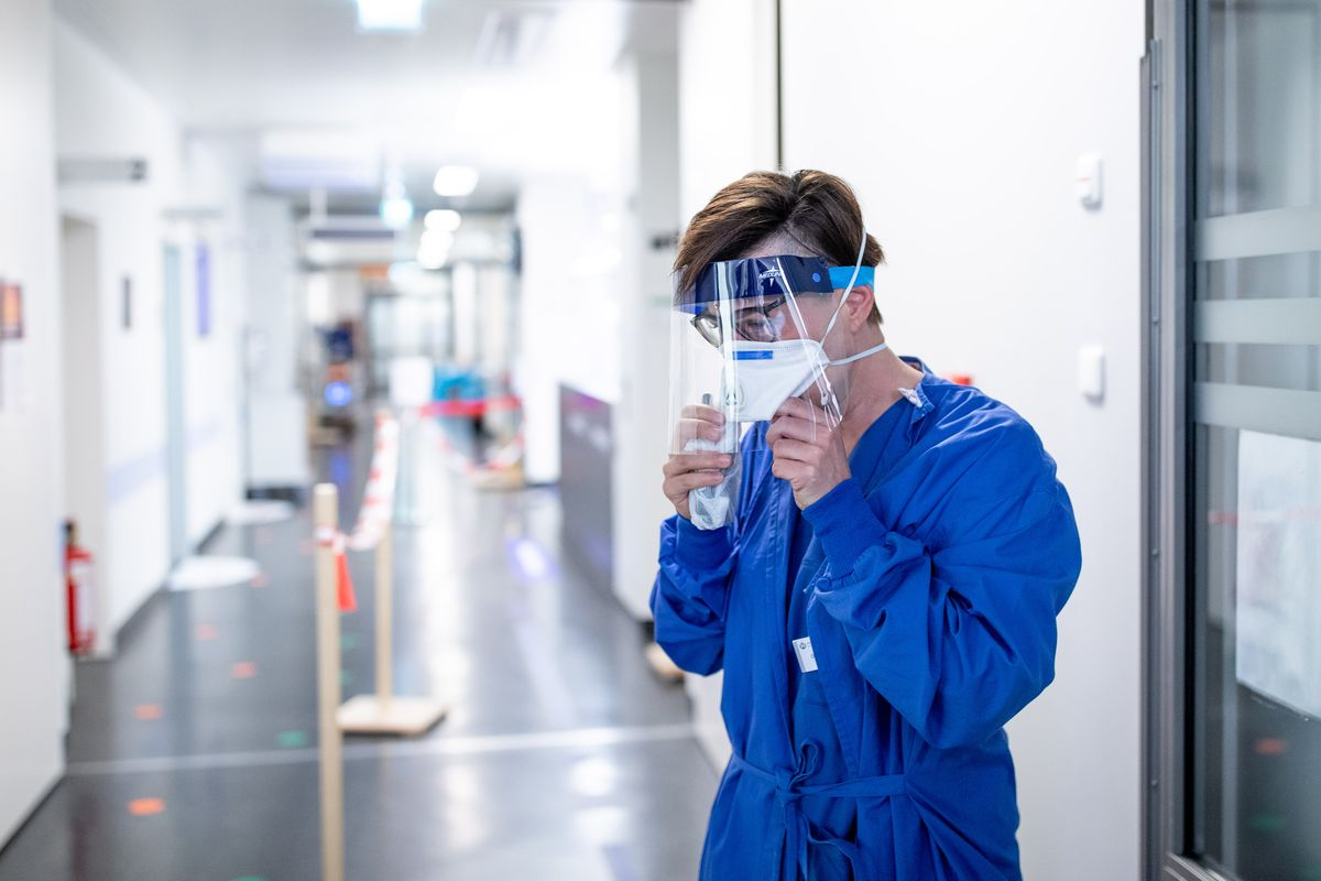 A medical professional in a mask standing in a hospital.