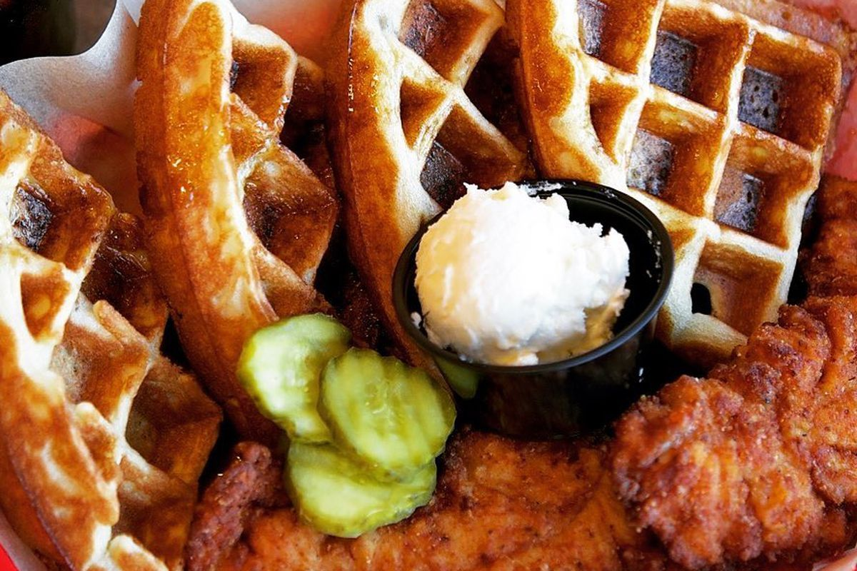 A bakset of spicy hot Nashville-style chicken, waffled, a small cup of butter and a few pickle slices on a red and white checkered paper lining.