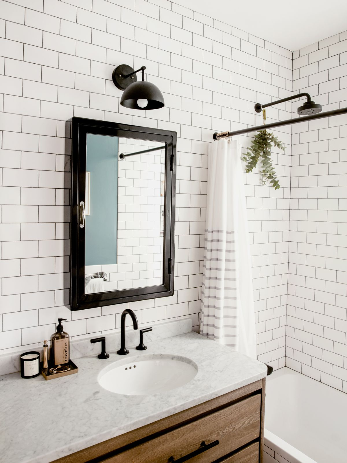A bathroom with a double sink, built in tub by the window, and black-rimmed mirror.